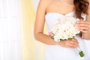 Bride holding wedding bouquet of white peonies, close-up, on light background